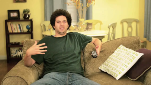 Joel sits on a couch, paunch a little too clear on camera.